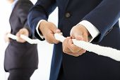 stock photo of tug-of-war  - Two businessman work together and playing tug of war in studio - JPG