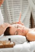 foto of ear candle  - Ear candling being carried out on an attractive caucasian woman in a spa - JPG