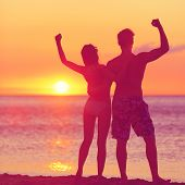 Winning success concept - happy beach couple at sunset with arms raised up outstretched cheering and