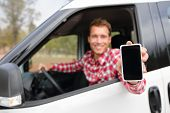 stock photo of driver  - Smart phone man in car driving showing smartphone display smiling happy - JPG