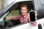 pic of driver  - Smartphone man in car driving showing smart phone display smiling happy - JPG