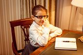 Girl In Eyeglasses Sitting Behind Table