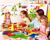stock photo of nursery school child  - Children  cutting out scissors paper in preschool - JPG