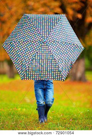 Boy Hiding Himself Behind The Umbrella