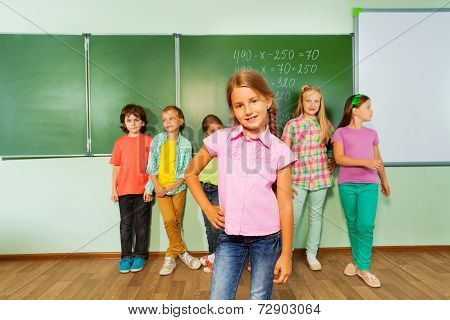 Girl stands near blackboard with numbers