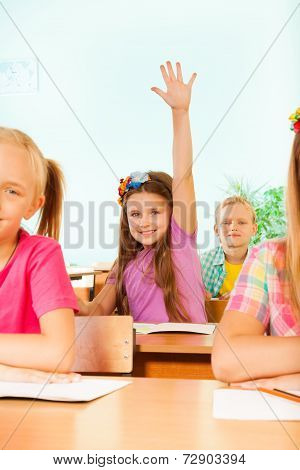 Smiling girl holds arm up behind her classmates