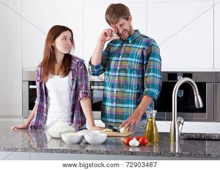 Couple Preparing Onion For Pizza