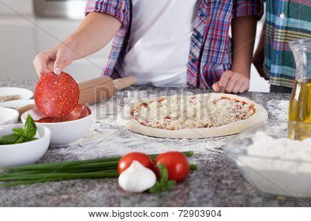 Preparing Pizza With Salami
