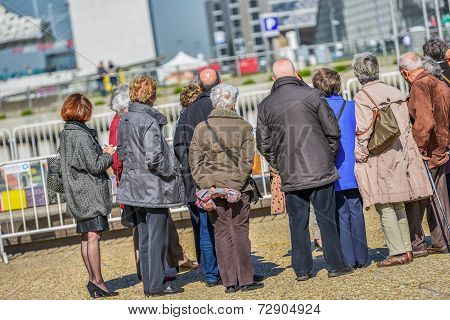 A Large Group Of Elderly Tourists Listening To The Guide