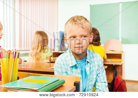 Boy sitting in school class and looking right