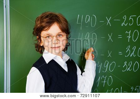 Clever boy holds chalk near blackboard