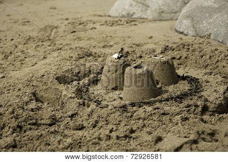 Three Simple Sandcastles on Beach