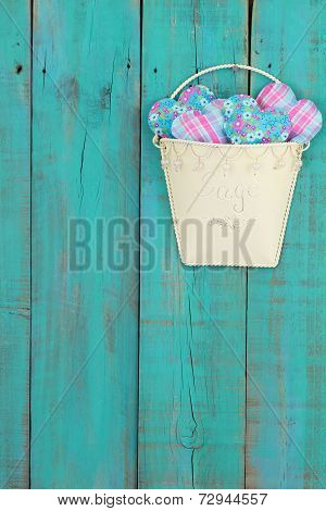 Tin pot of country hearts hanging on antique teal blue rustic wood fence
