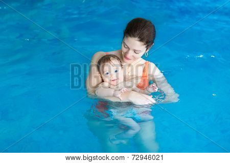 Young Mother And Her Baby Enjoying A Baby Swimming Lesson In The Pool