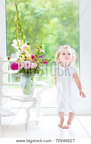 Beautiful Curly Baby Girl In A White Dress Playing Next To A Big Window And Door To The Garden