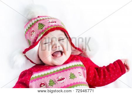 Funny Little Baby Laughing And Playing On A White Blanket Wearing A Christmas Decorated Knitted Hat