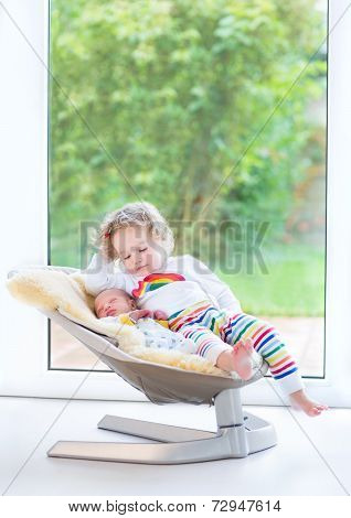 Newborn Baby Boy And His Toddler Sister Relaxing In Swing Next To Big Window And Door To The Garden