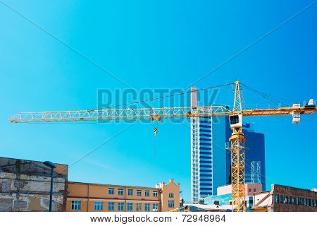 Construction Crane On Background Of New Modern Skyscraper And Old Buildings Intended For Demolition