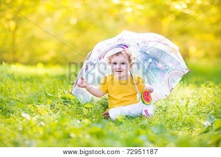 Cute Funny Baby Girl Playing In The Rain Under A Colorful Umbrella