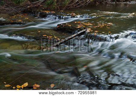 log in waterfalls in autumn