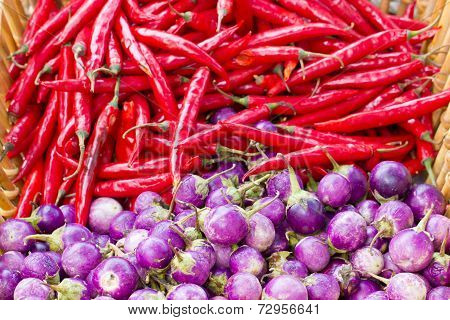 Heap of purple eggplant and red chili.