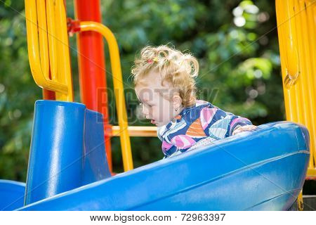 Happy Adorable Girl On Children's Slide On Playground Near Kindergarten Montessori On Summer Day
