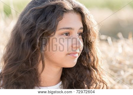 Teen Girl With Curly Dark Hair In  Nature