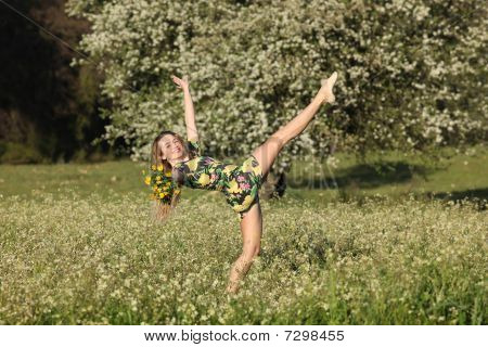 Beautiful Young Woman Stretching In Blooming Meadow