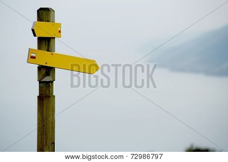 Yellow blank directions signs over cloudy sky, crossroad signpost, bright direction sign