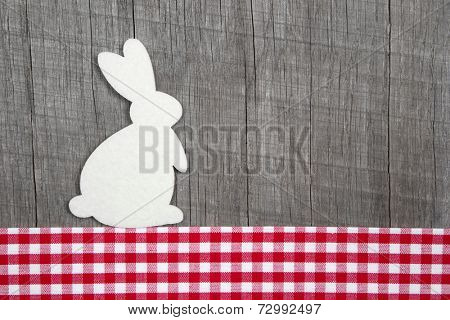 Easter decoration with a rabbit on a grey wooden background with a red checked ribbon
