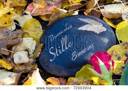Black grave stone in autumn with german words - decoration on a tomb for all saints day