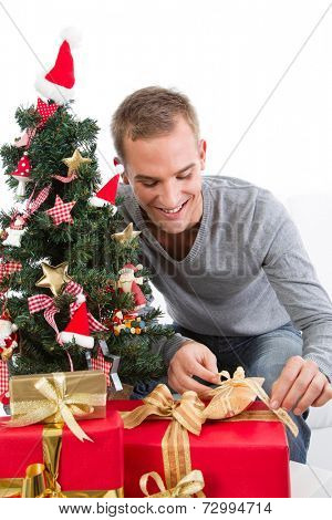 Smiling man unwrapping gifts