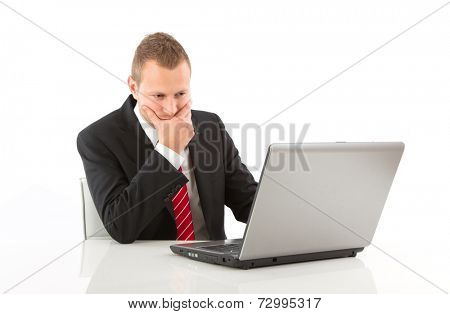 Caucasian businessman working on laptop and pondering