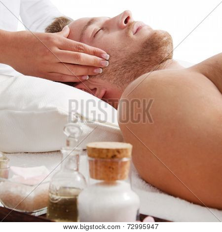 Side view of relaxed man getting scalp massage