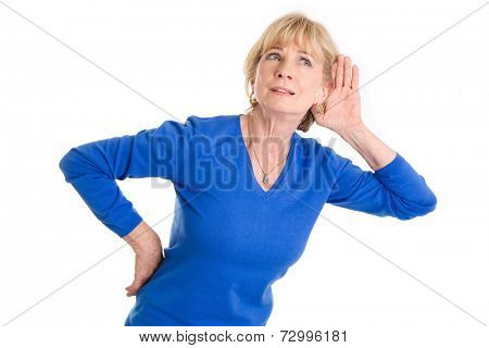 Older woman hearing isolated on white background wearing blue pullover.