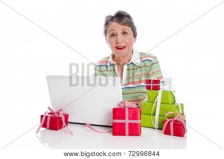 Older woman portrait: senior sitting at desk with laptop buying christmas presents.