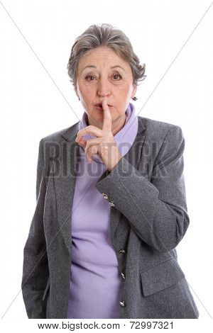 Caucasian elderly woman with finger on lips, isolated over white background.