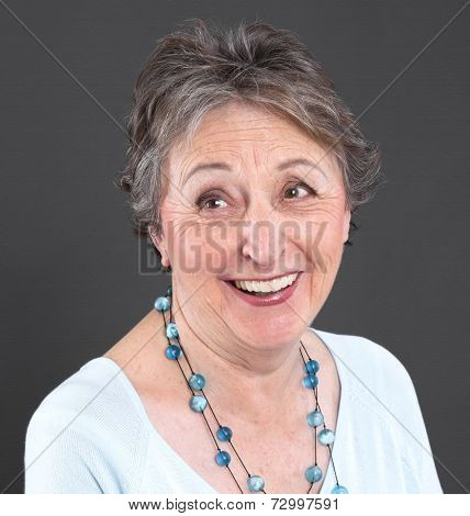 Portrait of a old smiling woman with the third teeths.