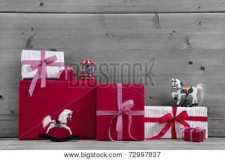Red Christmas presents and gift boxes with rocking horse on grey wooden background