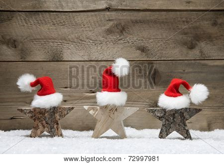 Three wooden stars with santa hats on wooden background - handmade idea for a greeting card