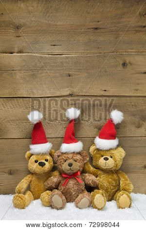 Three teddy bears with Christmas hats on wooden background for a greeting card