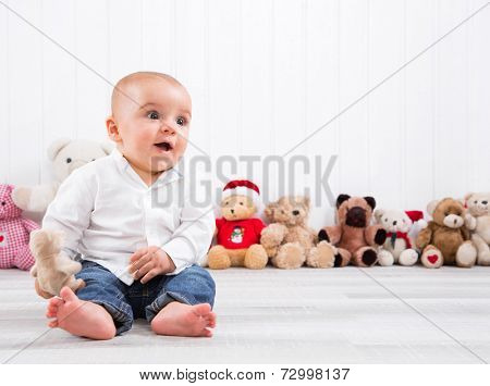 Barefoot baby on white background with cuddly toys - cute little boy