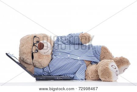 Over worked: teddy bear taking a nap on laptop isolated on white background