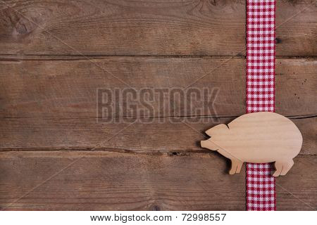 Wooden background with good luck pig on checkered ribbon or advertising for butcher