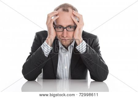 Frustrated businessman wearing glasses sitting at desk with head in hands isolated on white background
