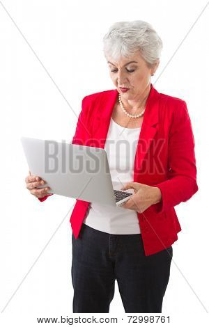 Senior businesswoman in red with lap top isolated on white background