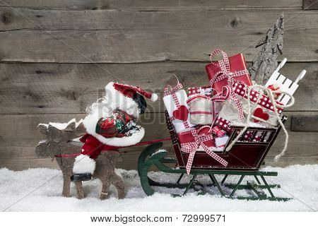 Christmas card decoration: elks pulling santa sleigh with presents on a wooden background - rustic country style greeting card