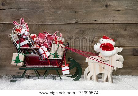 Christmas card decoration: elks pulling santa sleigh with presents on a wooden background - funny greeting card in Country Style