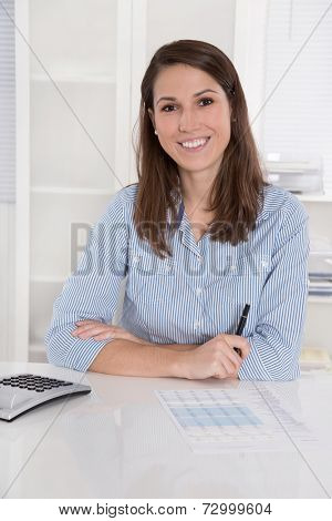 Successful business: woman smiling in blue blouse sitting at desk with folded arms