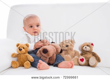 Amongst toys: cute baby sitting on white sofa with teddy bears